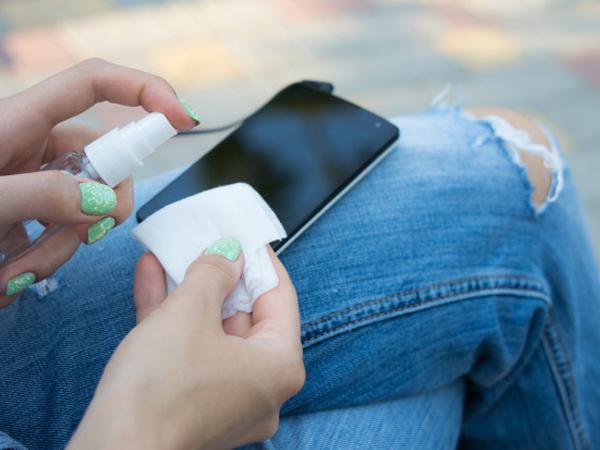 Membersihkan ponsel dengan cairan pembersih tangan