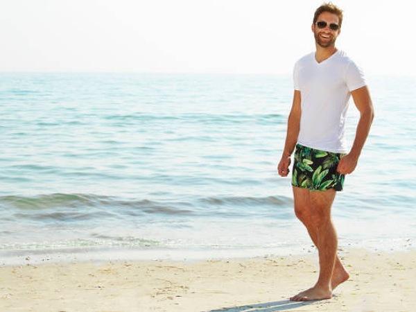 Ilustrasi pria dengan kaos polos dan celana pendek motif di pantai.